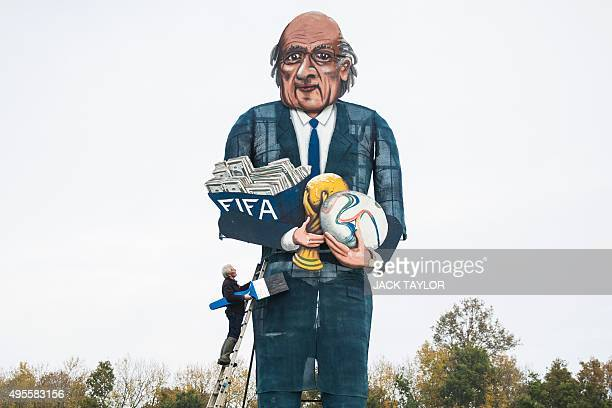 British artist Frank Shepherd of the Edenbridge Bonfire Society poses putting the finishing touches to a giant effigy of the suspended president of...