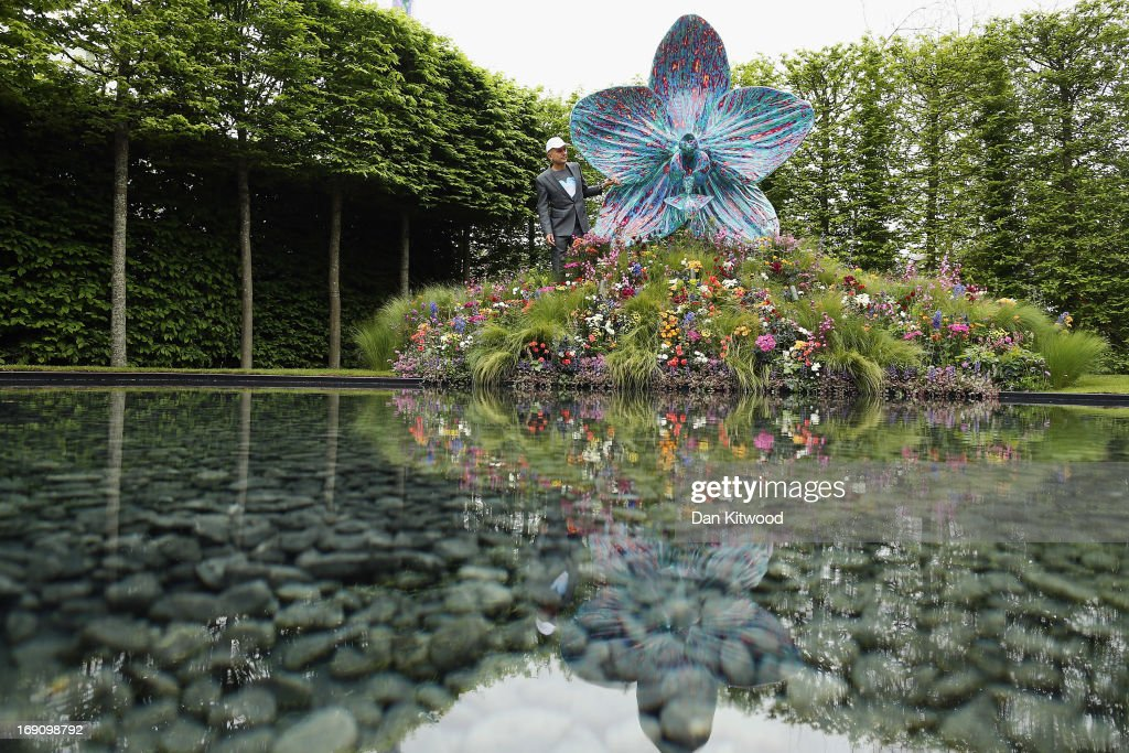 British artist <a gi-track='captionPersonalityLinkClicked' href=/galleries/search?phrase=Marc+Quinn&family=editorial&specificpeople=664862 ng-click='$event.stopPropagation()'>Marc Quinn</a> poses with his sculpture of an orchid in the Royal Horticultural Society (RHS) garden during the Chelsea Flower Show press day on May 20, 2013 in London, England. The Chelsea Flower Show run by the RHS, (Royal Horticultural Society) celebrates its 100th birthday this year.
