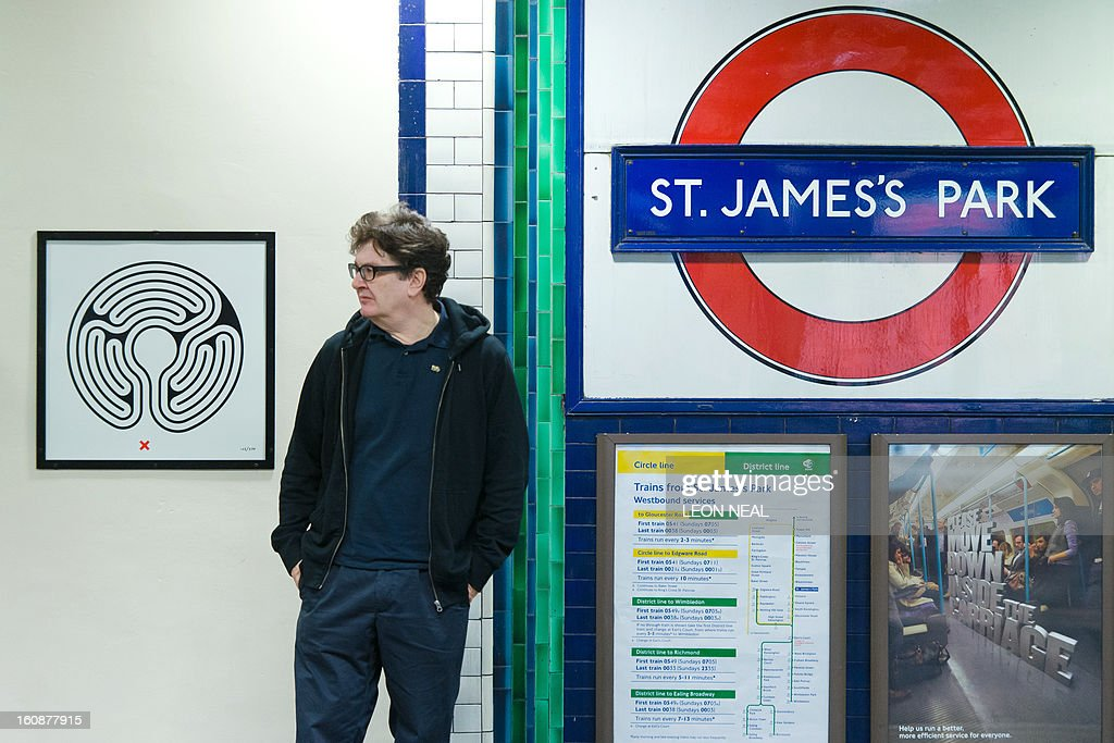 British artist Mark Wallinger poses with one of his paintings in St James Park tube station in central London on February 7, 2013 as part of the London Underground's 150th anniversary. The London Underground network has commissioned Wallinger to create a piece for each of it's 270 stations.