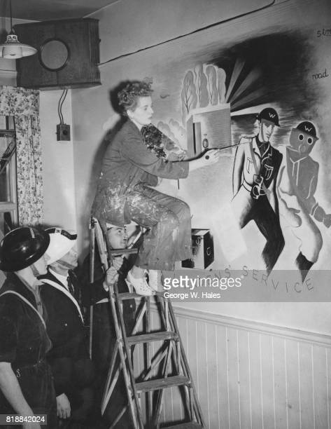 British artist Olga Lehmann works on a mural at the Wardens' Club at the St Pancras ARP headquarters in London 21st August 1940