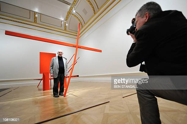 British artist Sir Anthony Caro poses for photographers with his sculpture entitled 'Early One Morning' during the press view of the 'Modern British...