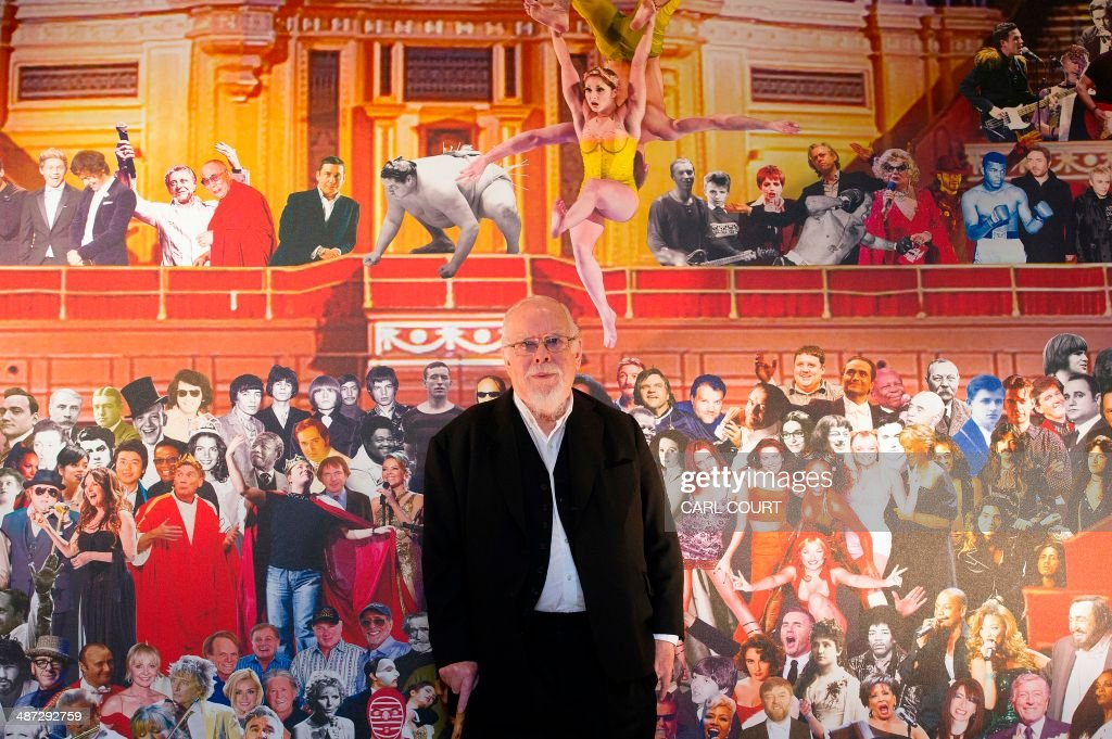 British artist Sir Peter Blake poses for pictures in front of his mural following its unveiling at the Royal Albert Hall in London on April 29, 2014. The Royal Albert Hall has been given the Sgt Pepper treatment by artist Sir Peter Blake, who has created a giant collage featuring some of the names who have graced the venue's stage. His triptych depicts figures from classical music, rock and sport who have made appearances under the dome of the London concert hall.