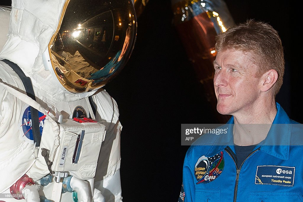 British astronaut Major Tim Peake (R) poses for photographs next to a spacesuit at the Science Museum in central London on May 20th 2013, where it was announced he will be joining the International Space Station (ISS) in late 2015. A former army helicopter pilot was on May 20 named as the first 'home-grown' British astronaut to head to the International Space Station. Major Tim Peake, 41, will fly out to the ISS in November 2015 as part of a six-man crew, becoming the first Briton ever to travel to space on a British government-funded mission.