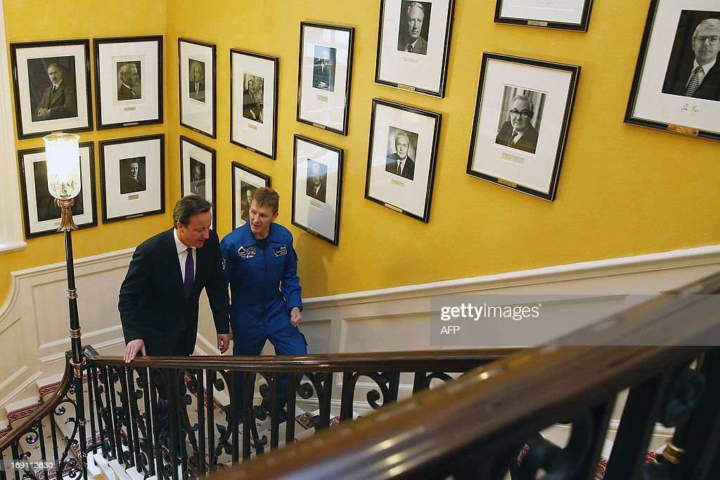 British astronaut Major Tim Peake (R) walks up the stairs with British Prime Minister David Cameron in 10 Downing Street in London on May 20, 2013. The former army helicopter pilot was on May 20 named as the first 'home-grown' British astronaut to head to the International Space Station. Major Tim Peake, 41, will fly out to the ISS in November 2015 as part of a six-man crew, becoming the first Briton ever to travel to space on a British government-funded mission. AFP PHOTO/POOL/DAN KITWOOD