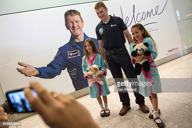 British astronaut Tim Peake has his picture taken with girls Roxanne and Layla Searle after he arrived at Heathrow Airport on a flight from Houston...