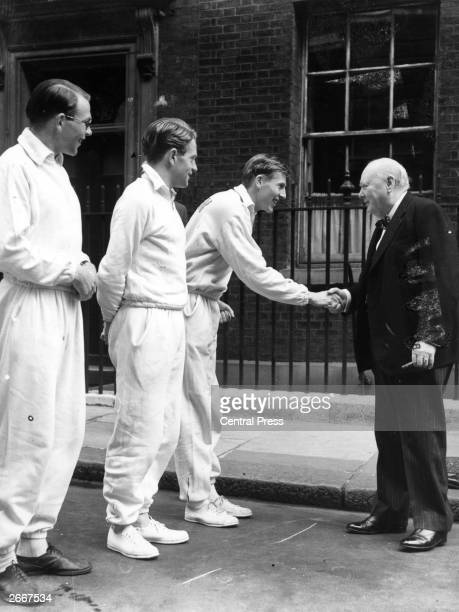 British athlete Roger Bannister shakes hands with Prime Minister Winston Churchill outside Downing Street in London as fellow runners Chris Brasher...