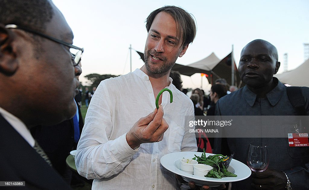 British author and anti-food waste campaigner Tristram Stuart (C) holds a rejected green beans on February 19, 2013 during the Governing Council of the United Nations Environment Programme (UNEP) at the UN headquarters in Nairobi, as he chats with delegates on the extent of food waste grown by Kenyan farmers but rejected by UK supermarkets due to cosmetic imperfections. The campaign aims to promote actions by consumers and food retailers to dramatically cut the 1.3 billion tonnes of food lost or wasted each year -- which, aside from the cost implications and environmental impacts, increases pressure on the already straining global food system –- and help shape a sustainable future. AFP PHOTO / SIMON MAINA