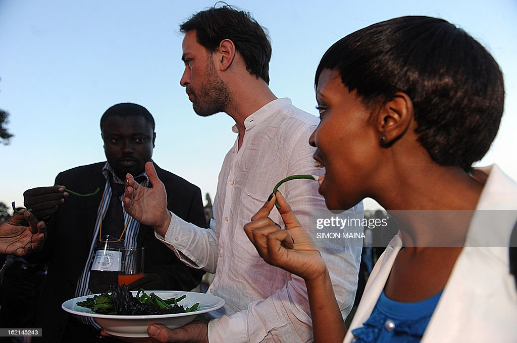 British author and anti-food waste campaigner Tristram Stuart (C) takes a bite of rejected green beans on February 19, 2013 during the UNEP Governing Council at the UN headquarters in Nairobi, as he chats with delegates on the extent of food waste grown by Kenyan farmers but rejected by UK supermarkets due to cosmetic imperfections. The campaign aims to promote actions by consumers and food retailers to dramatically cut the 1.3 billion tonnes of food lost or wasted each year -- which, aside from the cost implications and environmental impacts, increases pressure on the already straining global food system -- and help shape a sustainable future. AFP PHOTO / SIMON MAINA