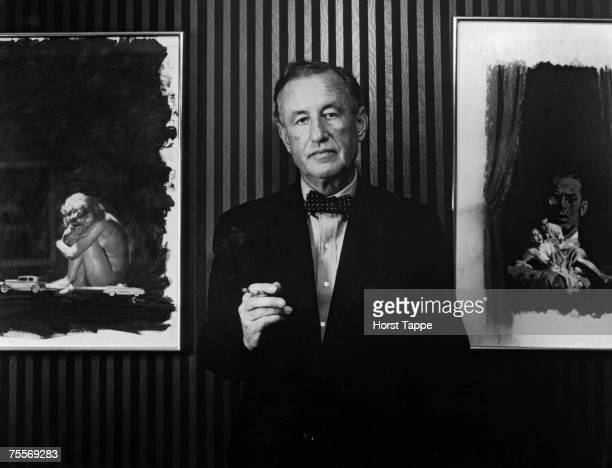 British author and creator of James Bond Ian Fleming with two pieces of original artwork from the American hardback editions of his books circa 1960