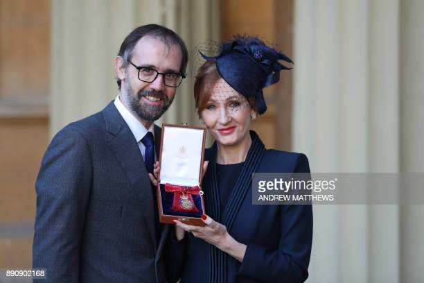 British author JK Rowling accompanied by her husband Neil Murray poses with her medal after being made a Companion of Honour for services to...