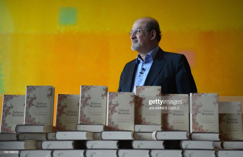 British author Salman Rushdie poses behind some copies of his book 'Joseph Anton' on October 1, 2012 in Berlin. As violent protests over a US-made film rock the Muslim world, Salman Rushdie publishes his account of the decade he spent in hiding while under a fatwa for his book 'The Satanic Verses'. AFP PHOTO / JOHANNES EISELE
