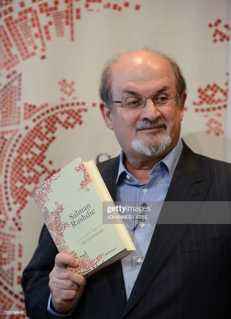 British author Salman Rushdie poses with a copy of his book 'Joseph Anton' on October 1, 2012 in Berlin. As violent protests over a US-made film rock the Muslim world, Salman Rushdie publishes his account of the decade he spent in hiding while under a fatwa for his book 'The Satanic Verses'.
