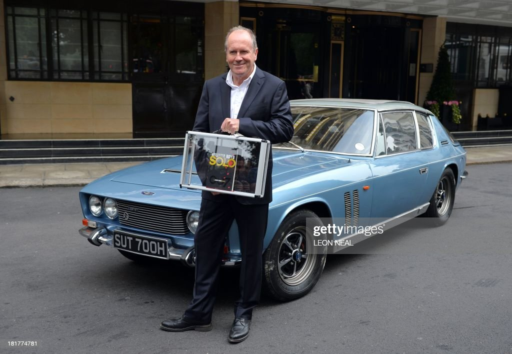 British author William Boyd poses with his new James Bond novel 'Solo' during a photo call a day ahead of its release in central London on September 25, 2013. Solo follows British agent 007 on an African adventure. AFP PHOTO/Leon Neal