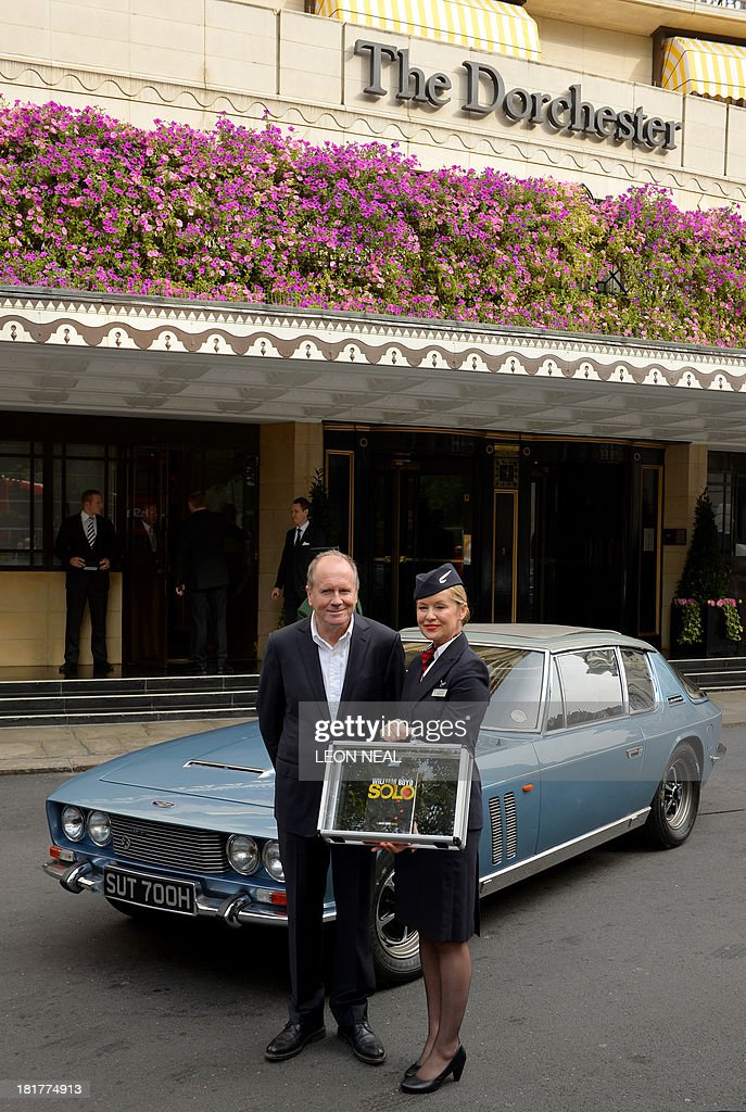British author William Boyd poses with his new James Bond novel 'Solo' and British Airways ambassador Helena Flynn during a photo call a day ahead of the its publishing in central London on September 25, 2013. Solo follows British agent 007 on an African adventure. AFP PHOTO/Leon Neal