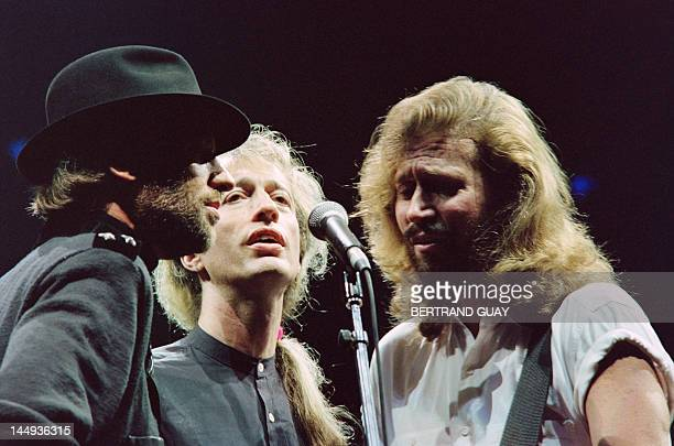 British band Bee Gees singer Robin Gibb flanked by his two brothers Maurice and Barry sings during a concert at Paris Bercy on June 23 1991 Gibb died...