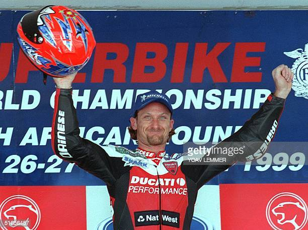 British biker Carl Fogarty of the Ducati team celebrates his victory in the first race of the superbike world championships on the Kyalami racetrack...