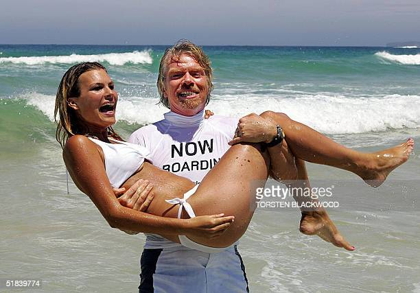 British billionaire Richard Branson carries model Ashleigh Warwick from the surf while promoting the maiden flight of his flagship airline Virgin...