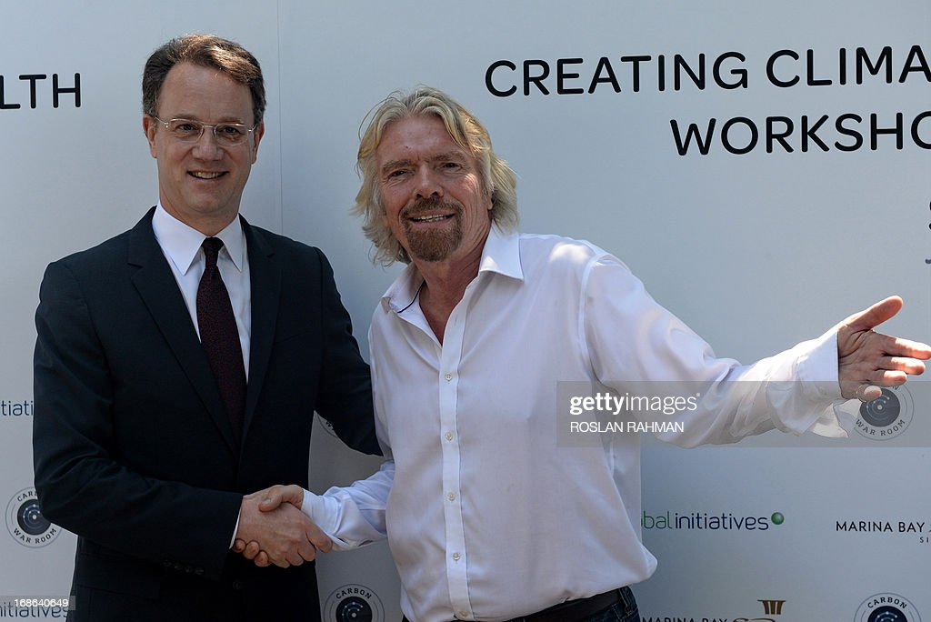 British billionaire Richard Branson (R) shakes hands with president and ceo of Marina Bay Sands, George Tanasijevich (L) on the rooftop garden of Marina Bay Sands hotel during a press conference in Singapore on May 13, 2013. Branson is in Singapore to attend the Creating Climate Wealth Workshops Summit organised by Carbon War Room from May 13 to 14.