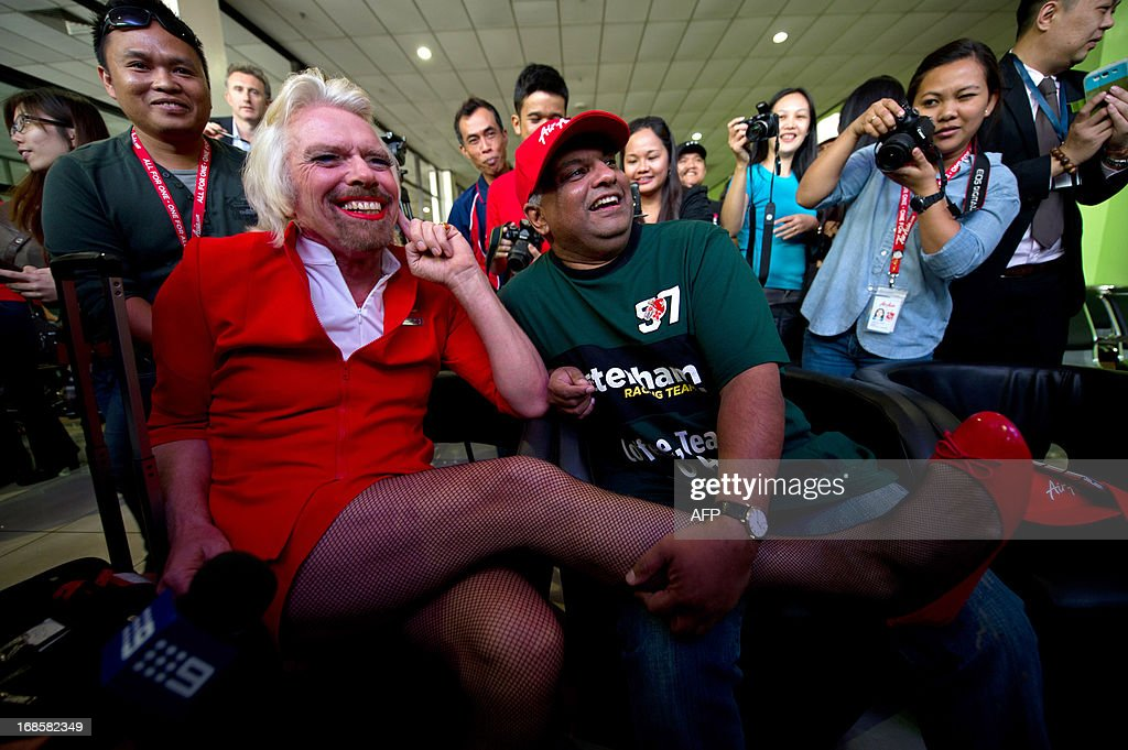 British billionaire Richard Branson (L) shares a light moment with AirAsia group chief Tony Fernandes (C) at the Low Cost Carrier Terminal (LCCT) in Sepang, outside Kuala Lumpur on May 12, 2013 after working as a flight attendant onboard an AirAsia flight from Perth. Branson honoured a losing bet with Fernandes over whose Formula One racing team would finish ahead of each other at the Abu Dhabi race during their debut 2010 season.