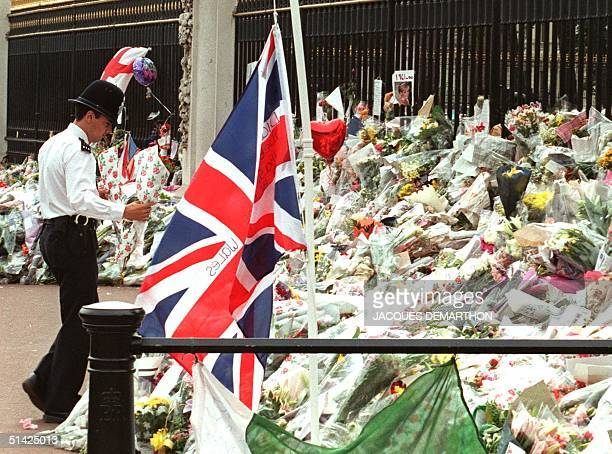 British bobby carries flowers to the gate of Buckingham Palace 05 September on the eve of the funeral of Diana Princess of Wales Diana died in a car...