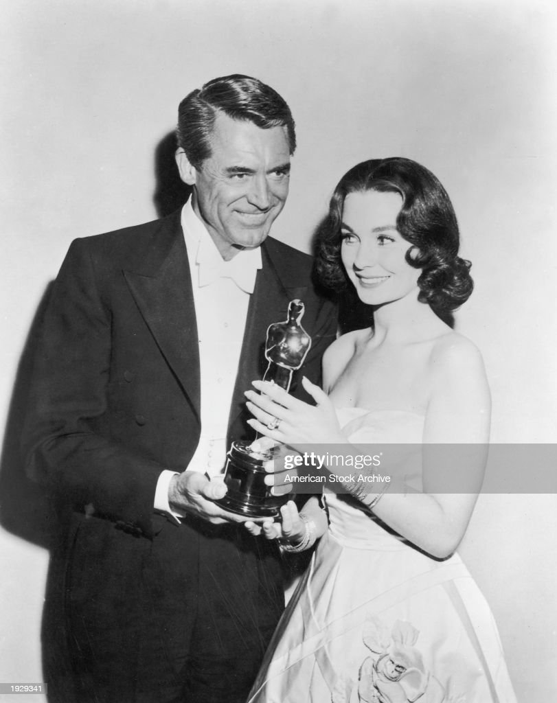 British born actor Cary Grant (1904 - 1986) presents British actor Jean Simmons with the Best Actor award, which she accepts on behalf of Alec Guinness for the film 'The Bridge on the River Kwai,' at the Academy Awards, Los Angeles, California, March 26, 1958.