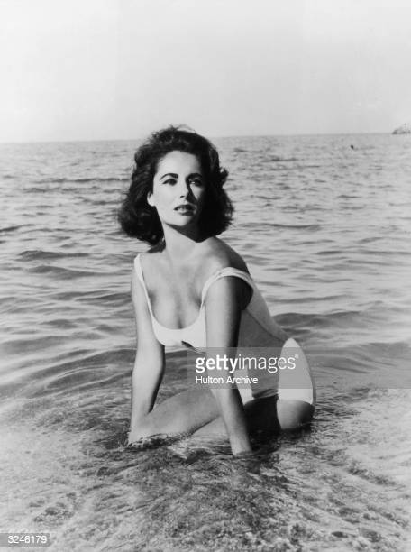 British born actor Elizabeth Taylor wears a white swimsuit while kneeling in the surf in a still from director Joseph L Mankiewicz's film 'Suddenly...