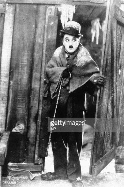 British born film star Charlie Chaplin appearing as his 'little tramp' character