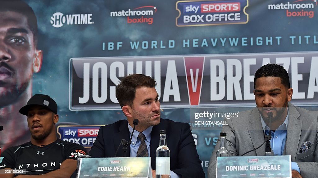 British boxer Anthony Joshua (L) and US boxer Dominic Breazeale (R) attend a press conference with promoter Eddie Hearn (C) for their forthcoming IBF World Heavyweight fight, in west London on May 4, 2016. Joshua, makes the first defence of his IBF Heavyweight World Championship against undefeated American challenger Dominic Breazeale in London on June 25, 2016. / AFP / BEN
