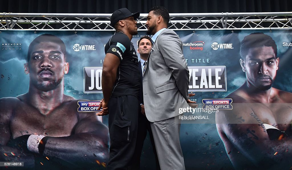 British boxer Anthony Joshua (L) and US boxer Dominic Breazeale (R) pose for photographers after holding a press conference for their forthcoming IBF World Heavyweight fight, in west London on May 4, 2016. Joshua, makes the first defence of his IBF Heavyweight World Championship against undefeated American challenger Dominic Breazeale in London on June 25, 2016. / AFP / BEN