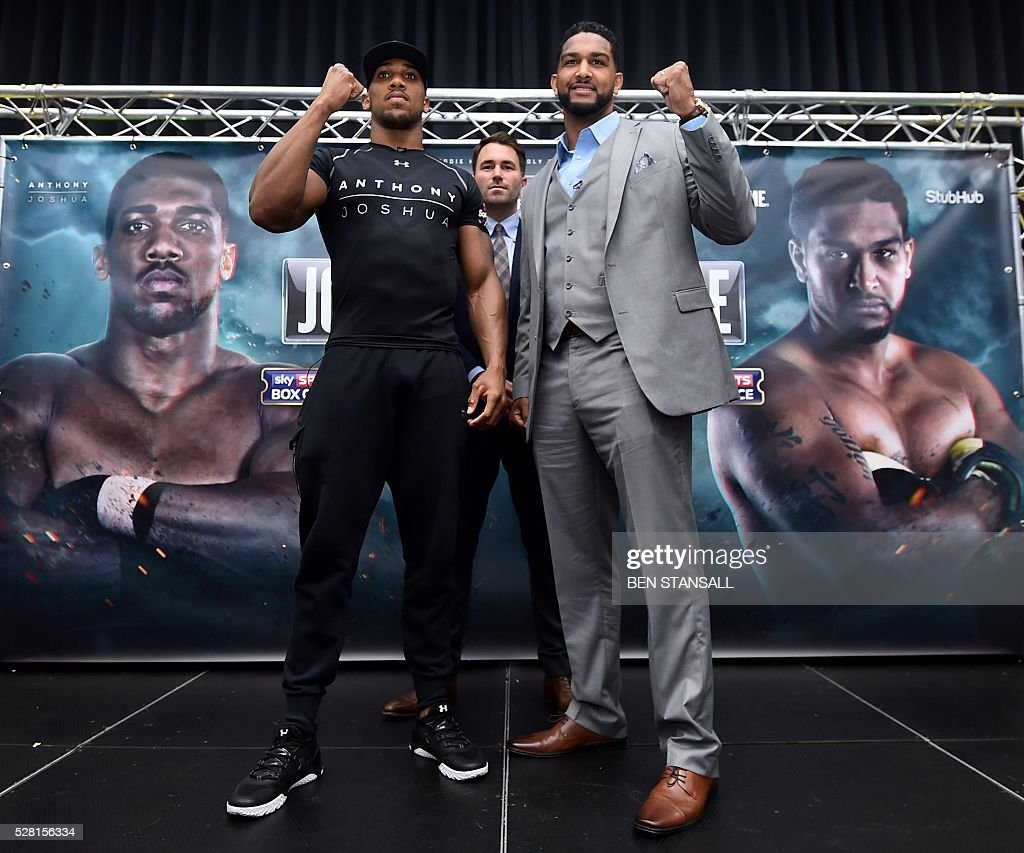 British boxer Anthony Joshua (L) and US boxer Dominic Breazeale (R) pose for photographers with promoter Eddie Hearn after holding a press conference for their forthcoming IBF World Heavyweight fight, in west London on May 4, 2016. Joshua, makes the first defence of his IBF Heavyweight World Championship against undefeated American challenger Dominic Breazeale in London on June 25, 2016. / AFP / BEN