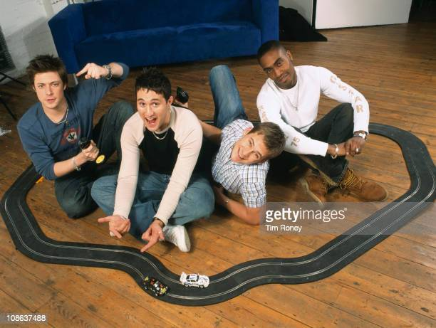 British boy band Blue with a model racing set London circa 2003 They are Simon Webbe Lee Ryan Duncan James and Antony Costa