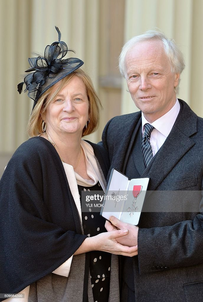 British broadcast journalist Geoff Meade (R) poses with his wife Jacki (L) and his medal after being appointed a Member of the Order of the British Empire (MBE) for services to the British community in Belgium at an investiture ceremony at Buckingham Palace in London on February 11, 2016. / AFP / POOL / Yui Mok