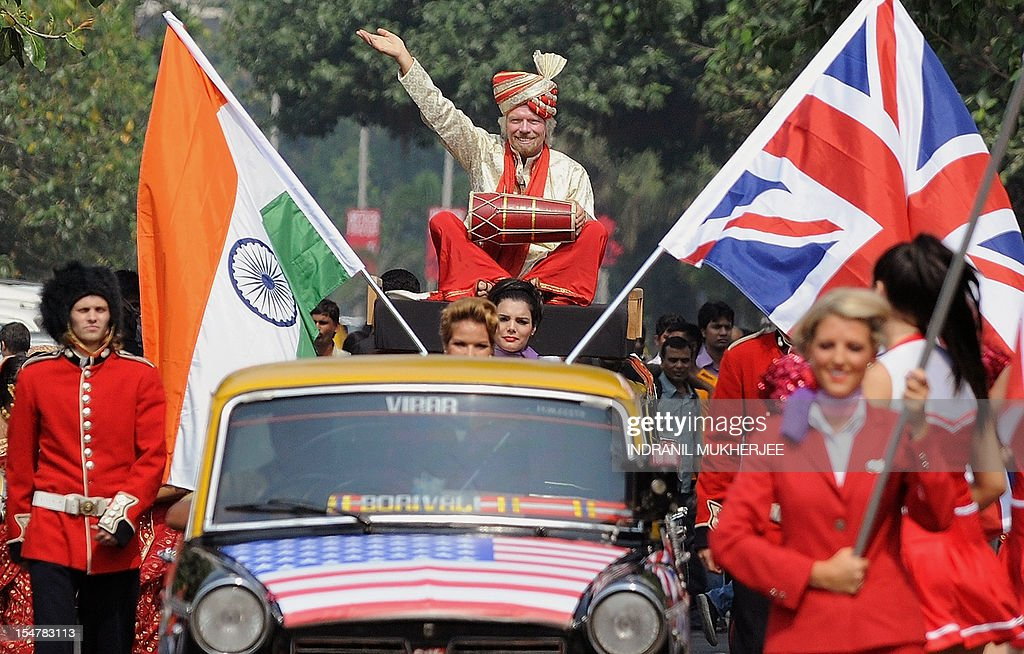 British business tycoon Richard Branson, sitting on top of a black-and-yellow city taxi, plays a traditional Indian drum during a photo opportunity parade in Mumbai on October 26, 2012. Branson is in the city to announce the launch of Virgin Atlantic's new service from Mumbai to London and connecting on to US cities New York, Boston, Washington DC, and Miami.