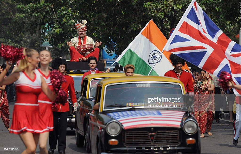 British business tycoon Richard Branson, sitting on top of a black-and-yellow city taxi, plays a traditional Indian drum during a photo opportunity parade in Mumbai on October 26, 2012. Branson is in the city to announce the launch of Virgin Atlantic's new service from Mumbai to London and connecting on to US cities New York, Boston, Washington DC, and Miami. AFP PHOTO/ INDRANIL MUKHERJEE