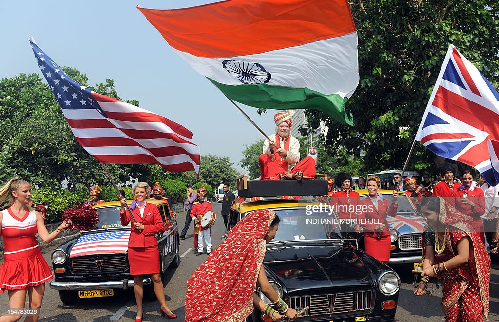 British business tycoon Richard Branson, sitting on top of a black-and-yellow city taxi, waves the Indian national flag during a photo opportunity parade in Mumbai on October 26, 2012. Branson is in the city to announce the launch of Virgin Atlantic's new service from Mumbai to London and connecting on to US cities New York, Boston, Washington DC, and Miami.