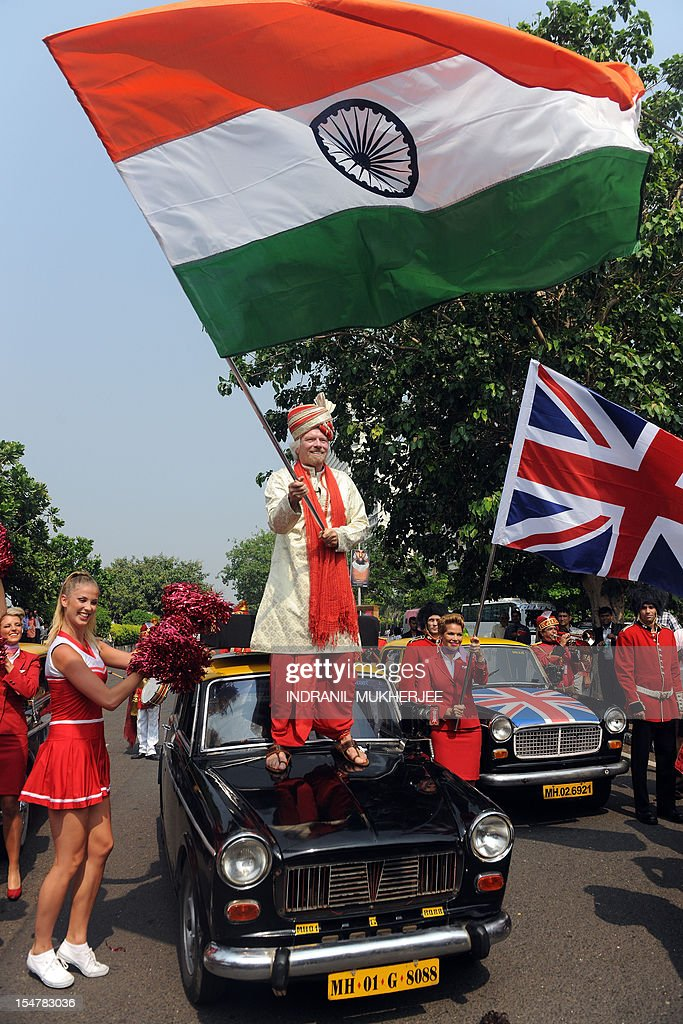 British business tycoon Richard Branson, standing on top of a black-and-yellow city taxi, waves the Indian national flag during a photo opportunity parade in Mumbai on October 26, 2012. Branson is in the city to announce the launch of Virgin Atlantic's new service from Mumbai to London and connecting on to US cities New York, Boston, Washington DC, and Miami. AFP PHOTO/ INDRANIL MUKHERJEE