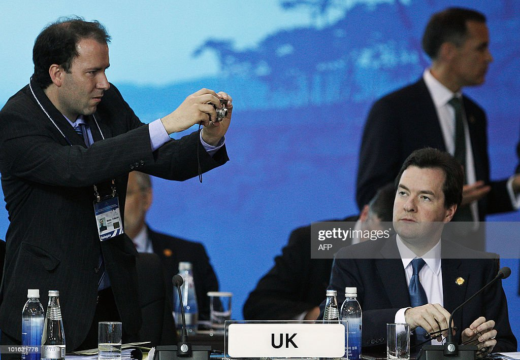 British Chancellor of the Exchequer, George Osborne, (R) looks at delegate taking a photograph during a break at the G20 Finance Ministers and Central Bank Governors Meeting in Busan on June 5, 2010. Finance ministers from the world's leading nations sought to narrow differences on key banking reforms, wrapping up a two-day meeting aimed at safeguarding fragile economic recovery.