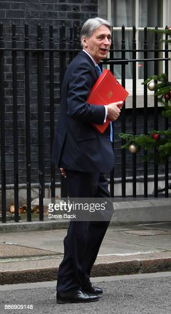 British Chancellor of the Exchequer Philip Hammond leaves for Prime Minister's Questions as he walks to a car in Downing Street on December 6 2017 in...