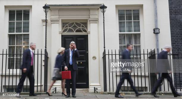 TOPSHOT British Chancellor of the Exchequer Philip Hammond scratches his head as he waits for his ministerial team to depart before posing with the...
