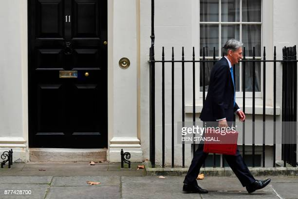 British Chancellor of the Exchequer Philip Hammond walks away after posing for pictures with the Budget Box as he leaves 11 Downing Street in London...