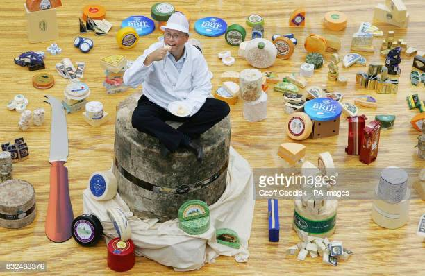 British cheese producer Peter Mitchell sits on top of a half tonne Mature Farmhouse Cheddar which forms part of the World`s Largest Cheese Board...