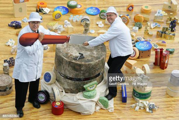 British cheese producers Nigel White and Peter Mitchell slice into a half tonne Mature Farmhouse Cheddar which forms part of the World`s Largest...