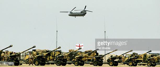 British Chinook helicopter flies over cannons at Camp Gibraltar February 24 2003 near Kuwait City Kuwait British Defense Secretary Geoff Hoon is...