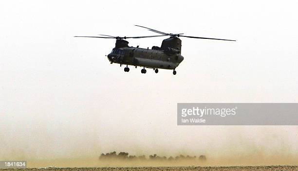 British Chinook helicopter from the Joint Helicopter Force hovers over huddled troops from 51 Squadron Royal Air Force Regiment March 11 2003 in the...