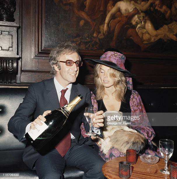 British comedian and actor Peter Sellers pouring a glass of champagne as he sits beside his wife Australian fashion model Miranda Quarry at the...