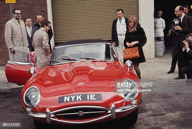 British comedian and actor Peter Sellers presents a gift of a red Jaguar EType car to his girlfriend Britt Ekland at Heathrow airport in London on...