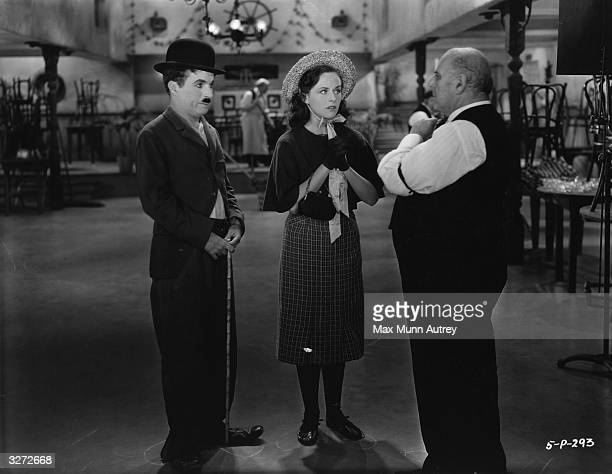 British comedian and director Charles Chaplin and actress Paulette Goddard to whom he was married for seven years star with beefy actor Henry Bergman...