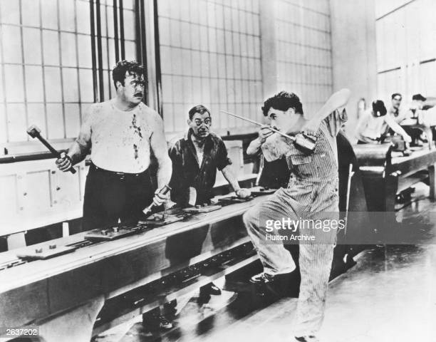 British comedian and director Charlie Chaplin about to start a fight on a factory production line in a scene from the film 'Modern Times'