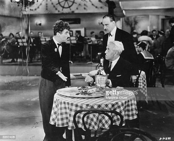 British comedian and director Charlie Chaplin has a disagreement with the head waiter and a customer in his cafe in a scene from the film 'Modern...