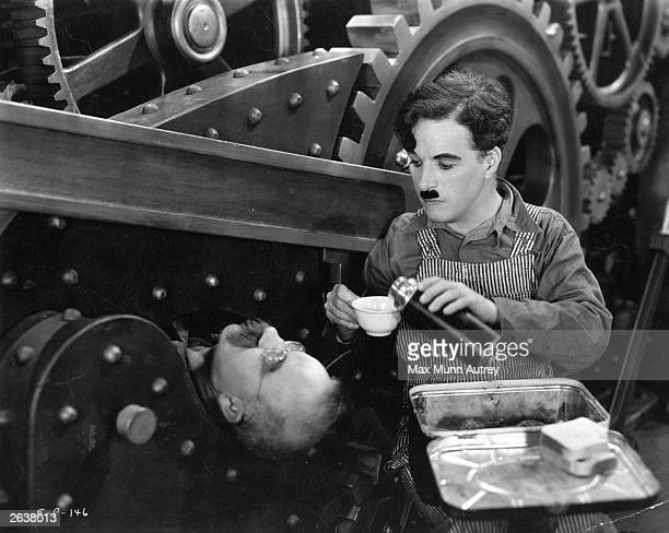 British comedian and director Charlie Chaplin pours a drink from a flask for Chester Conklin who is imprisoned by a piece of industrial machinery in...